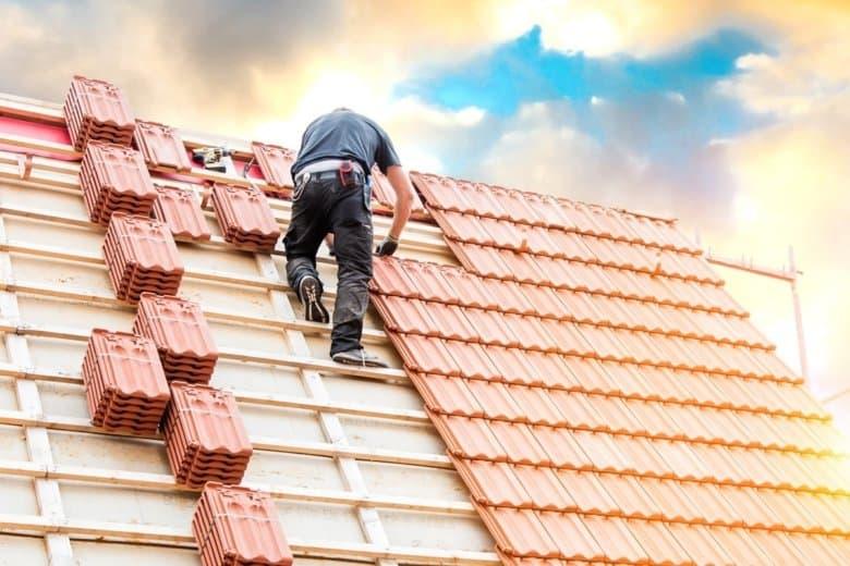 Dachdecker auf dem Dach mit Dachziegelstapeln