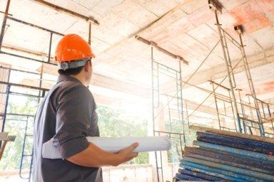 Bausachverständiger auf Baustelle mit Plan in der der Hand