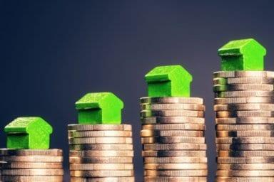 Das Eigenkapital dargestellt als Holzhäuser auf Münzen