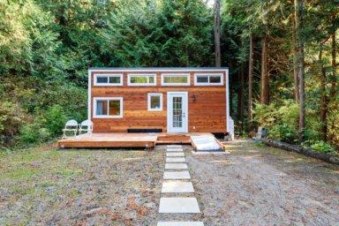 Tiny House im Wald mit Fentern und Weg zum Hause