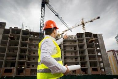 Bausachverständiger mit Helm, zeigt auf Rohbau während einer Qualitätskontrolle