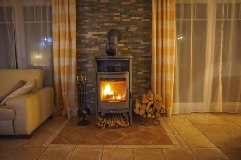 Brennender Kaminofen im Wohnzimmer - Gemütliche Stunden vor dem Kamin sind gerade in der kalten Jahreszeit sehr reizvoll.