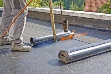Dachdecker schweißt Dachbahnen auf Flachdach
