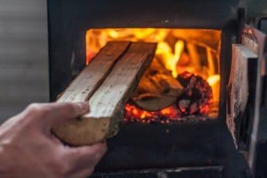 Mann, der Holz in Kaminofen nachlegt