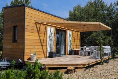 Tiny House aus Holz mit Terrasse im Sonnenschein