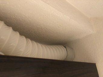 Abluft einer Dunstabzugshaube nach draußen über einem Küchenschrank