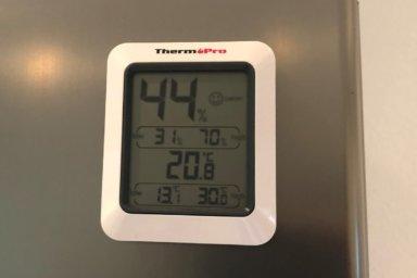 Ein Thermohygrometer mit Magnet an einem Kühlschrank in der Küche