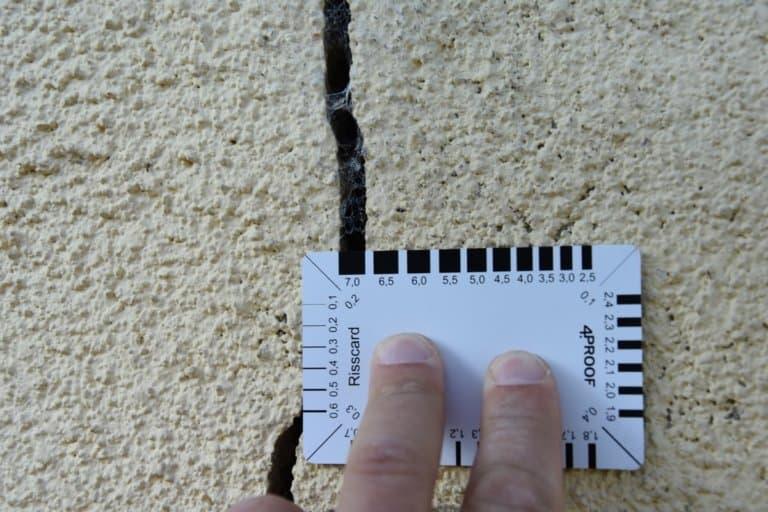 Ein Riss im Mauerwerk, 7 mm breit, mit Rissbreitenkarte gemessen