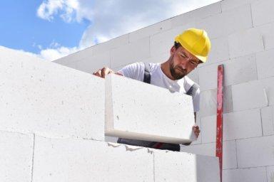 Maurer erstellt Mauerwerk aus Porenbeton mit Dünnbettmörtel