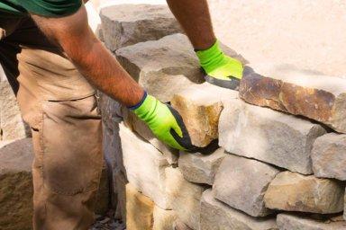 Ein Maurer baut im Garten eine Trockenmauer aus Naturstein