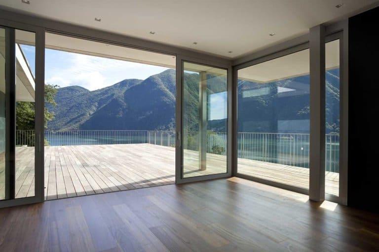 Große Eckfenster mit Schiebeelement vom Wohnzimmer zur Terrasse mit Aussicht auf einen See