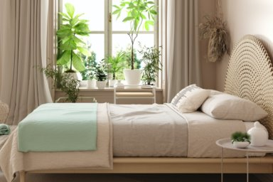 Schlafzimmer mit großem Fenster, Pflanzen und Blick ins Grüne