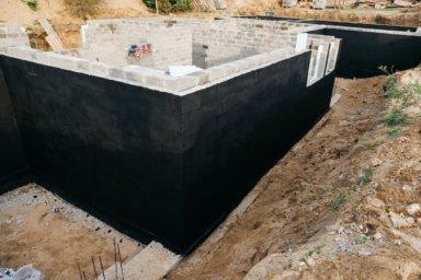 Die erste Lage Schwarzabdichtung der Kellerwände