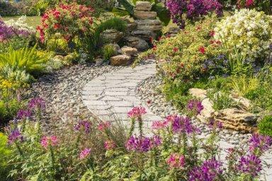 Ein Gartenweg aus Natursteinplatten mit vielen blühenden Blumen