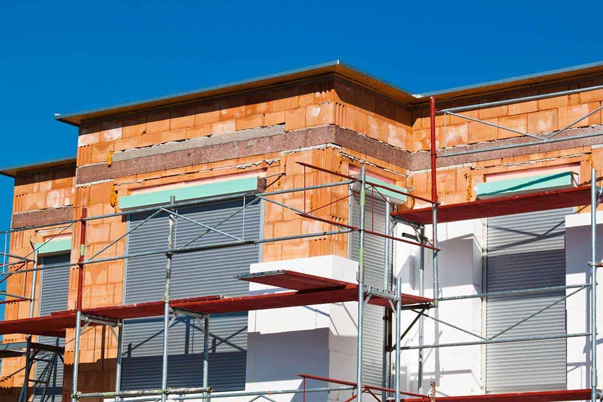 Ein Neubau bei dem EPS-Wärmedämmung auf Ziegelmauerwerk aufgeklebt wird