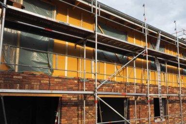 An einer Hauswand wird eine Klinkerfassade mit Kerndämmung hochgezogen