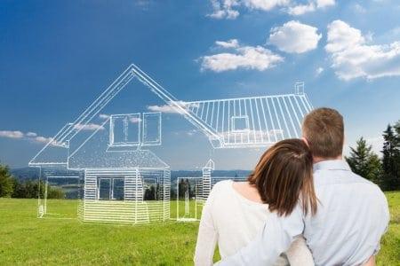 Paar steht vor der Skizze eines Hauses auf einer grünen Wiese.