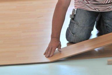 Ein Handwerker verlegt Laminat