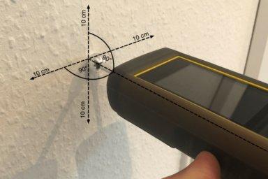 Das Feuchtemessgerät TROTEC T660 wird senkrecht auf die Wand gehalten, um die Wandfeuchte zu messen