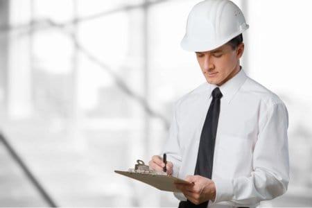 Bausachverständiger mit Helm macht Notizen