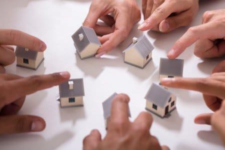 Viele Hände halten kleine Modellhäuser