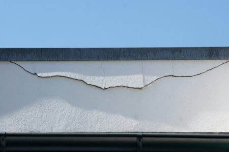 Ein breiter Putzriss in der Fassade unter der Attika