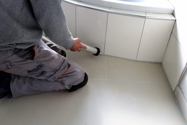 Ein Handwerker verfugt Fliesen im Badezimmer