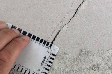 Ein Riss im Kalksandstein, 2,5 mm breit mit Rissbreitenkarte gemessen.