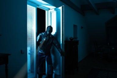 Ein Einbrecher bricht durch ein Fenster in ein Haus ein