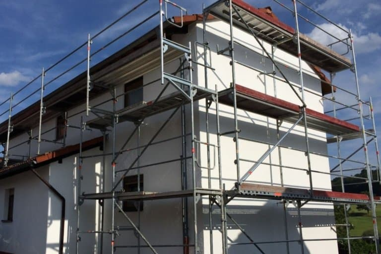 Eine frisch gestrichene Fassade eines Einfamilienhauses mit Gerüst.