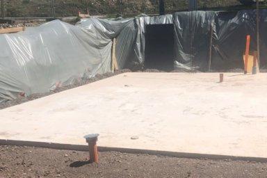 Eine Baugrube mit Bodenplatte. Die Böschung ist mit Planen vor Durchfeuchtung geschützt.