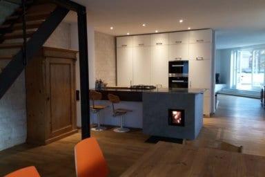 Das Bild zeigt einen Kachelherd mit einer Kochplatte und Backröhre, die mit der Holzfeuerung beheizt werden. So kann ein Kachelofen in die (Wohn-)Küche integriert werden.