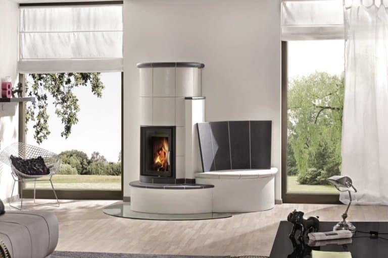 Ein moderner Kachelofen mit Sitzbank. Durch eine große Sichtscheibe ist das Feuer zu sehen Durch helle Keramikplatten und zeitlos schlichtes Design passt der Kachelofen gut zum Stil der Einrichtung und ist ein echter Hingucker.