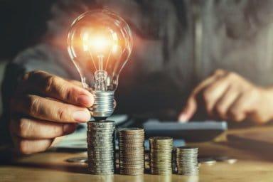 Ein Geschäftsmann hält eine Glühbirne auf einem Stapel Münzen
