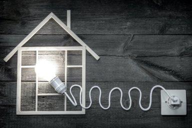 Eine Glühbirne, die mit einem Kabel an eine Steckdose angeschlossen ist, erhellt ein Modelhaus