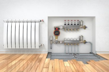 Heizkreisverteiler mit Fußbodenheizung neben einem Heizkörper im Raum.