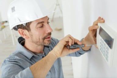 Ein Installateur befestigt die Steuerung für die Heizung