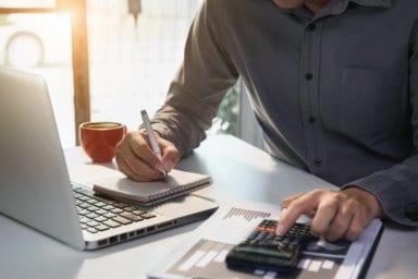Ein Mann am Schreibtisch mit Taschenrechner kalkuliert die Kosten für ein neues Badezimmer.