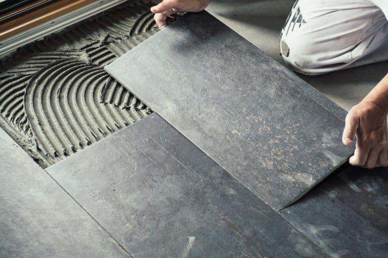 Ein Arbeiter verlegt Bodenfliesen