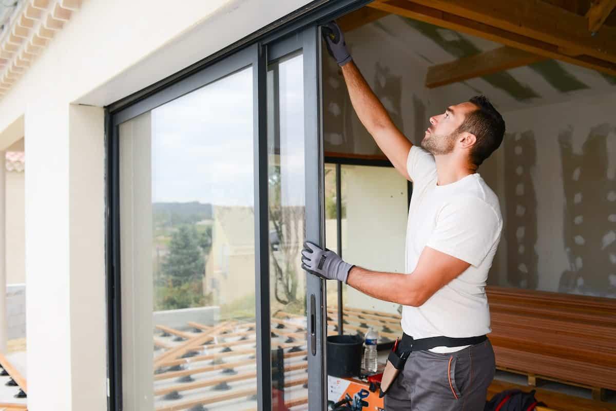 Ein Handwerker überprüft Fenster und Türen eines Neubaus