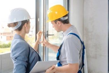 Eine Architektin und ein Handwerker überprüfen Fenster auf der Baustelle