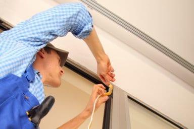 Ein Handwerker erneuert die Fensterdichtung