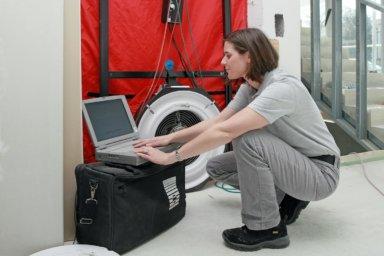 Ein Technikerin führt einen Blower-Door-Test durch