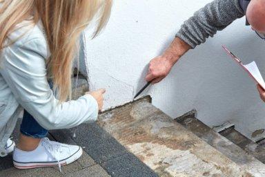 Ein Sachverständiger erklärt einer Kundin das Problem mit der Feuchtigkeit am Sockel vom Haus
