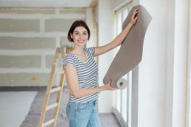 Ein Frau auf der Baustelle wählt eine Tapete aus