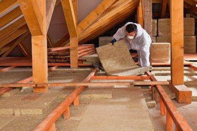 Ein Handwerker verlegt Wärmedämmung im Dachgeschoss