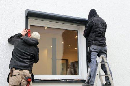 Zwei Arbeiter montieren eine Rollladenkasten