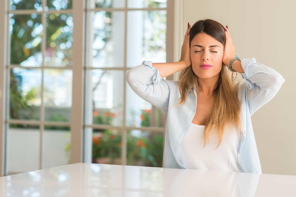Eine Frau hält sich die Ohren wegen zu lauten Geräuschen zu