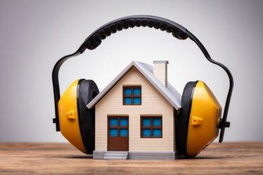Ein Modellhaus mit Arbeitsschutz-Kopfhörer